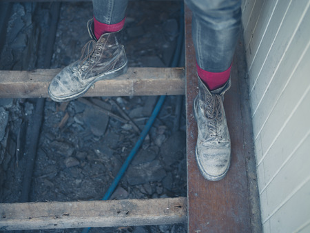 dirty feet: The feet of a worker wearing dirty old boots standing on the floor joists in a house undergoing renovations Stock Photo