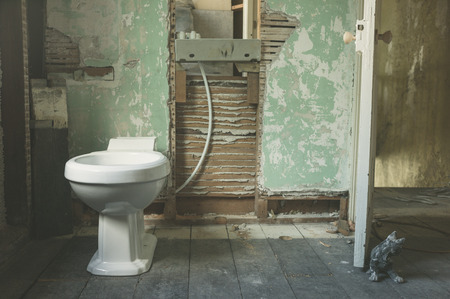 A brand new toilet fitted in an old derelict room being converted to a bathroom Stock Photo
