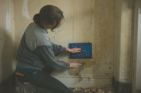 removing: A young woman is removing wallpaper with a steamer