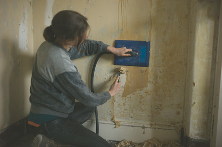 A young woman is removing wallpaper with a steamer