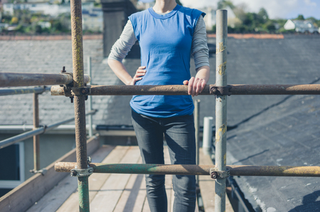 scaffold: A young woman is standing on a scaffold by a roof Stock Photo