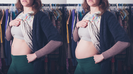 baby wardrobe: A young pregnant woman is standing at home in her walk-in wardrobe and is trying to hide her baby bump
