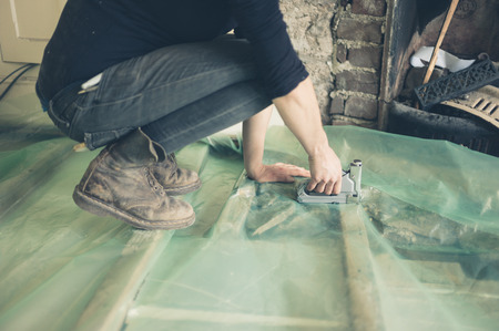 barrier: A young woman is putting down a vapor barrier and insulating a floor Stock Photo