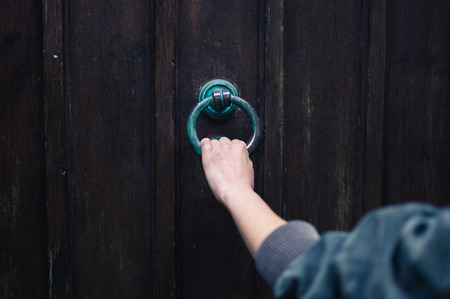 The hand of a young woman is grabbing a knocker on an old wooden door