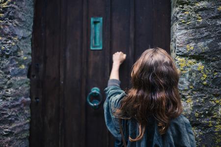 tocar la puerta: Una mujer joven está llamando a una puerta de madera vieja