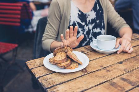 グルテン自由な食事療法で若い女性がカフェでトーストのおかげで言ってないです。