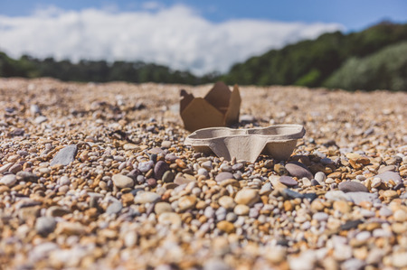 wrappers: Empty food wrappers abandoned on a pebble beach Stock Photo