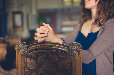 pews: A young woman is sitting with her hands folded and is praying in a church