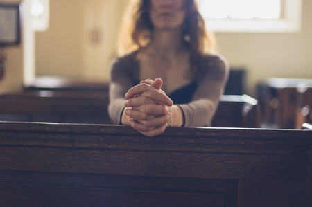 A young woman is sitting with her hands folded and is praying in a church