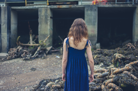 trash the dress: A young woman wearing a dress is exploring a shipyard with rusty old anchors