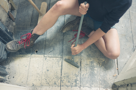 floorboards: A young woman is sitting on the floor and is removing paint from the floorboards