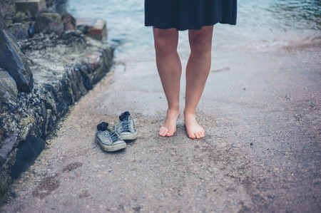 slipway: A barefoot woman standing on slipway with her shoes Stock Photo