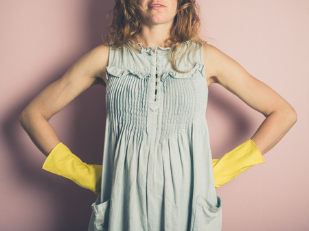estereotipo: A young woman is wearing yellow rubber gloves Foto de archivo