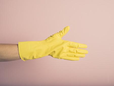 estereotipo: Una mano con un guante de goma amarillo está ofreciendo un apretón de manos
