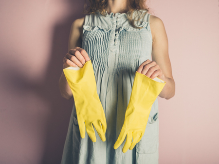 estereotipo: A young woman holding a pair of rubber gloves