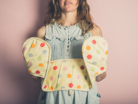 estereotipo: A young woman is posing with oven gloves against pink background