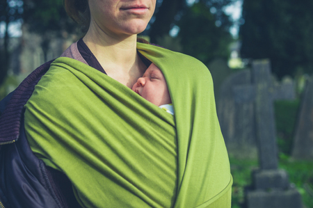 A young mother is standing in a cemetary with her baby in a sling
