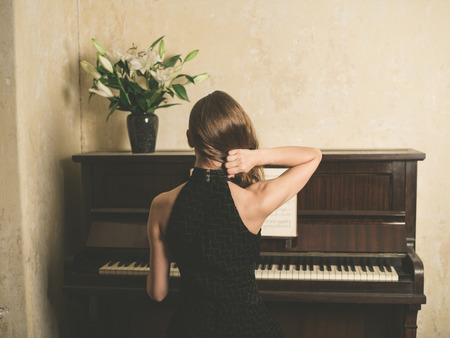 A beautiful young woman in a dress is sitting at a piano Stock Photo