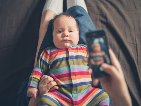 A mother is using her smartphone to take a photo of her baby Stock Photo