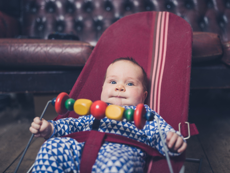 A baby is sitting in a vintage bouncy chair on the wooden floor