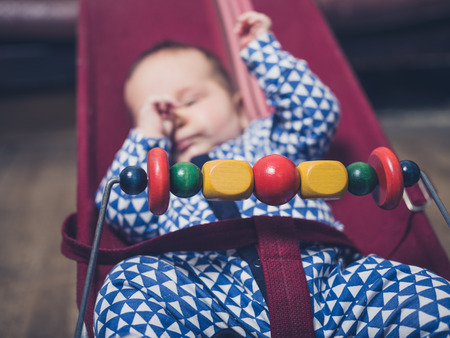 A tired baby is sitting in a vintage bouncy chair Stock Photo