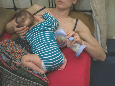 A young mother in bed is breastfeding her baby whilst expressing milk with a pump