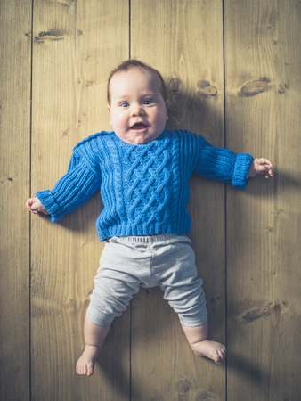 floorboards: A happy and surprised baby lying on a wooden floor Stock Photo