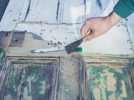 A male hand is scraping paint from an old door