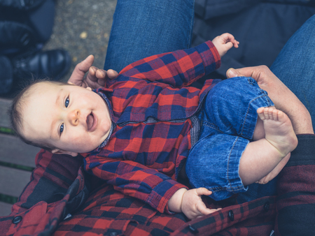 A young father is sitting outside with his baby son in his lap wearing a matching outfit photo