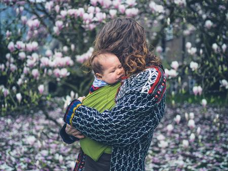 Una joven madre con su bebé llorando en un cabestrillo está de pie junto a un árbol de magnolia