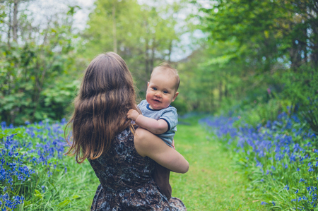 A young woman is sitting in a meadow with her baby Stock Photo