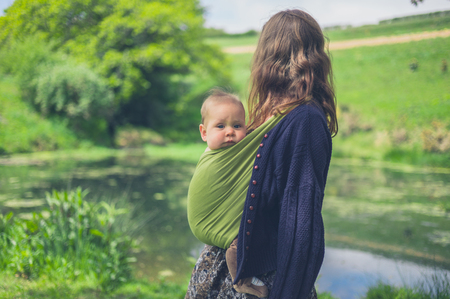 A young woman with a baby in a sling is standing by a pond in the countryside