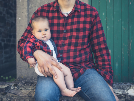 identical: A young father and his baby son are sitting outside wearing identical shirts