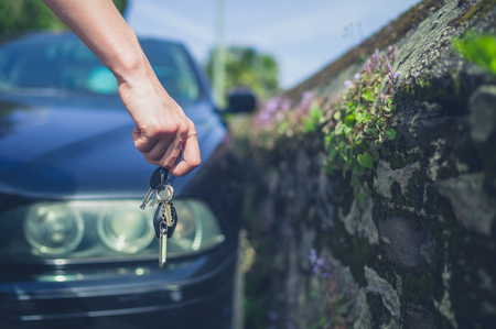 A young female hand is holding some car keys by a vehicle