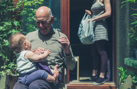 A grandfather is sitting in a backyard with his baby grandson