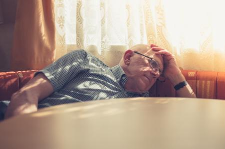 悲しい、疲れた老人は日差しの中でウィンドウが頭を休んでいます。 写真素材