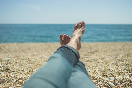 The feet of a young man as he is resting on the beach photo