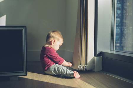 duplex: A little baby is sitting by the window in a high rise apartment
