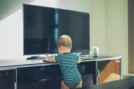 modern living room: A little baby is cruising on the furniture by the television