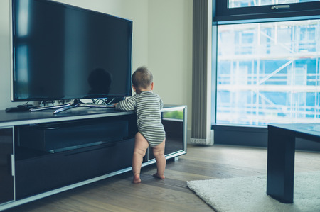 modern living room: A cute little baby is crusing on the television furniture in a city apartment