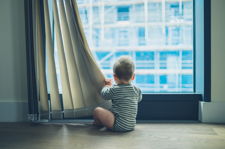 A little baby is playing with the curtain in a high rise apartment Standard-Bild