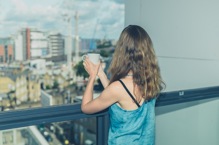 balcony: A young woman is drinking a cup of coffee on her balcony in the city