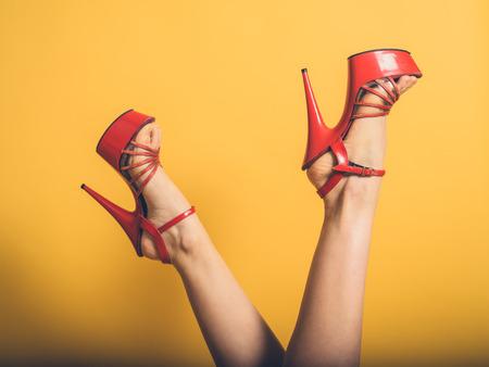 Een jonge vrouw draagt rode stripperhielen en heft haar benen in de lucht op