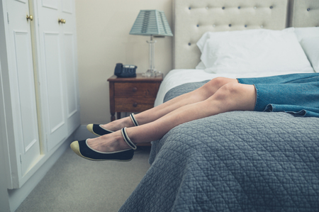 The legs and feet of a young woman relaxing on a bed Stock Photo