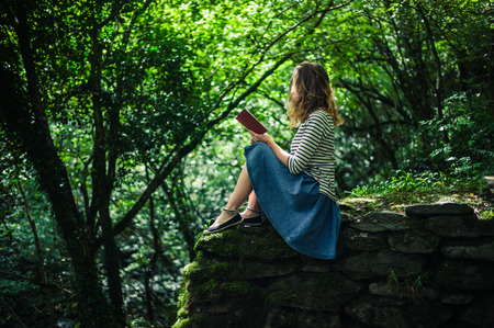A young woman is sitting on a wall in the forest and is reading a book Stock Photo