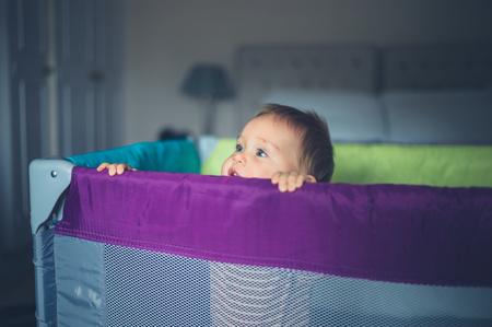 행복한 작은 아기가 그의 playpen에 서서 측면을 찾고 있습니다.