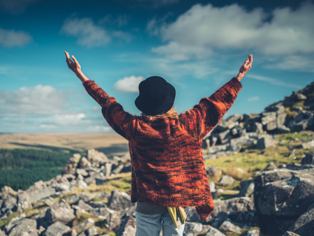 A young woman wearing a hat is raising her arms in the wilderness Stock Photo