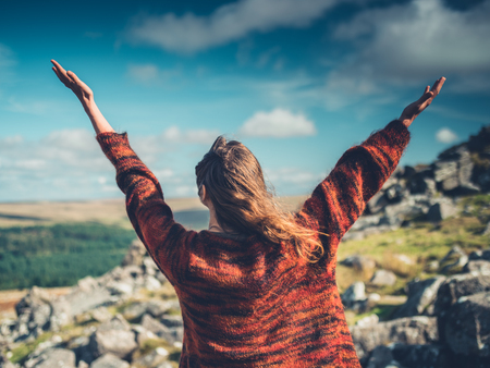 A young woman is raising her arms in the wilderness