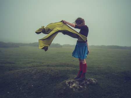 A young woman with a long scarf blowing in the wind is standing on the moor in the fog Standard-Bild - 88131233