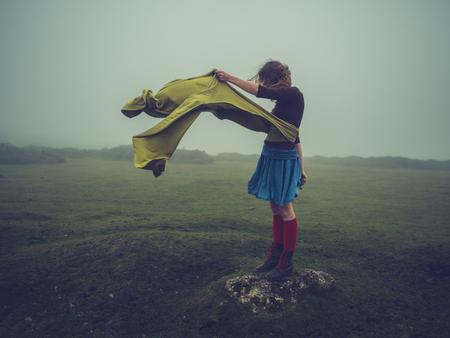 Eine junge Frau mit einem langen Schal weht im Wind steht auf dem Moor im Nebel Standard-Bild - 88131233